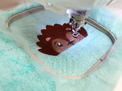 Free project instructions to embroider a terrycloth baby bib with a stitch-filled embroidery design.