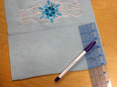 Free project instructions to embroider a hooded fleece scarf.