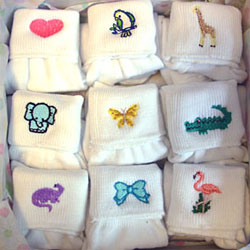 White socks with cuffs embroidered with miniature animal designs.