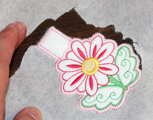 Free project instructions for stitching machine embroidered clothespin cozies or covers.