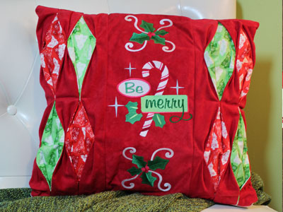 Free project instructions to create a Be Merry Pleat Pillow.
