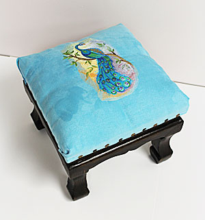 Free project instructions to upholster a stool with embroidery.