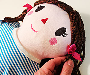 Free project instructions to make an embroidered soft rag doll.