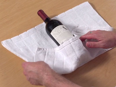 Free project instructions to embroider a kitchen towel bottle wrap.