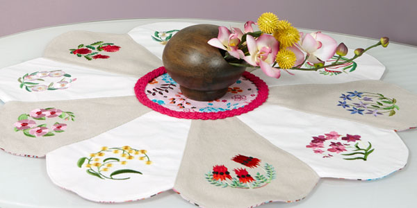 Free project instructions to embroider a pretty petals table topper.