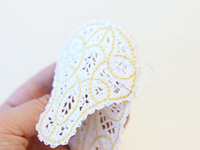 Free project instructions to create a freestanding Battenburg lace baby bootie.