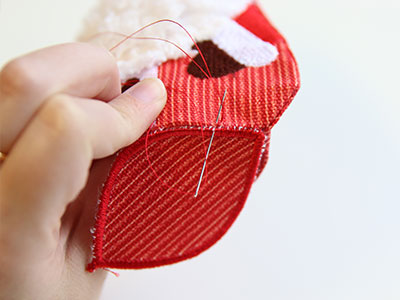 Free project instructions to stitch an in-the-hoop primitive Santa stuffie.