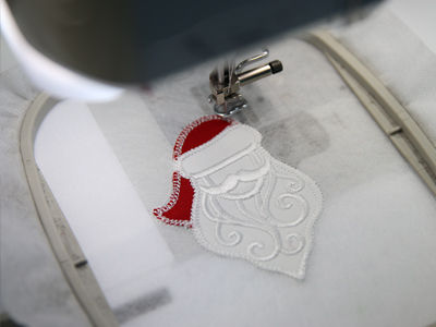 Free project instructions to create a freestanding lace and fabric Santa decoration.
