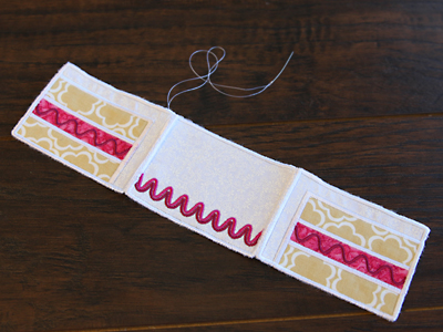 Free project instructions to create an embroidered in-the-hoop cake pincushion.