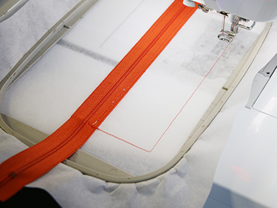 Free project instructions for creating in-the-hoop zipper-back pouches.
