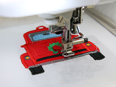 Free project instructions for creating an in-the-hoop retro truck gift card holder.