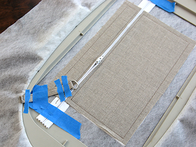 Free project instructions for creating an in-the-hoop lace front lined zipper pouch.