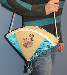 Free project instructions for an Asian style fan-shaped purse embellished with machine embroidery design.