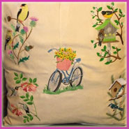 A pillow embroidered with birds, birdhouses, and bicycles.