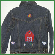 A red barn embroidered on a denim jacket back.