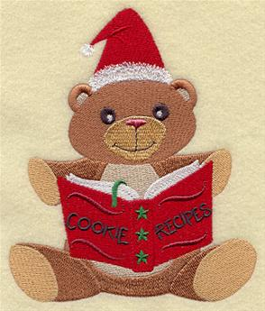 A Christmas baking bear reads a recipe machine embroidery design.