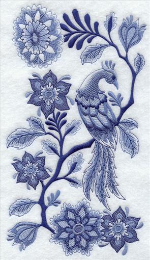 A bird with fancy plumage sits on a flowering branch in a lovely Delft blue machine embroidery design.