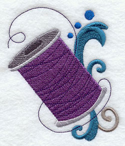 A spool of thread and filigree machine embroidery design.
