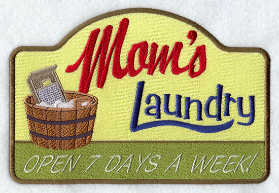 A vintage machine embroidery sign that says Mom's Laundry...open 7 days a week.