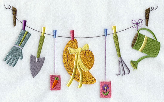 A gardener's gloves, hat, watering can, spade, and flower seeds hang from a clothesline machine embroidery design.