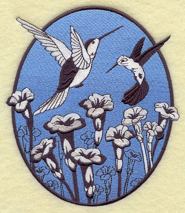A spring oval machine embroidery design with black and white flowers and hummingbirds against a lightly colored backdrop.