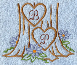 A two hearts carved into a tree embroidery design monogrammed with an alphabet.