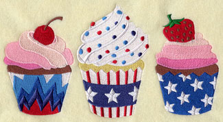 Three cupcakes with red, white, and blue Fourth of July frosting and decorations.