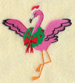 A Christmas flamingo wears a Santa hat and wreath.