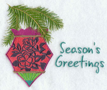 "An ornament with an hibiscus silhouette hangs from a pine bough with the words ""Season's Greetings."""