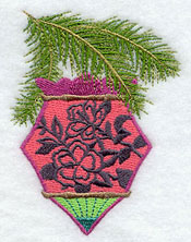 An ornament with an hibiscus silhouette hangs from a pine bough.