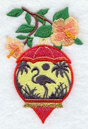 A flamingo beach silhouette scene inside a hibiscus-decorated ornament.