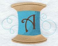 Machine embroidery spool of thread alphabet.