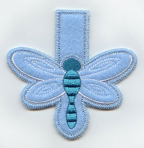 An in-the-hoop machine embroidery dragonfly clothespin cover.