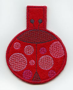 An in-the-hoop machine embroidery ladybug clothespin cover.